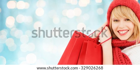 winter, sale, people and holidays concept - woman in red hat and scarf with many shopping bags over blue lights background
