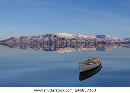 Winter Scape with Snowy Mountains and a Boat on a Calm Lake  - stock photo