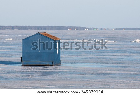 Winter scene: blue ice fishing house on frozen lake - stock photo