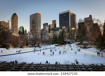 Winter scene in Central Park: the Wollman Rink at sunset. Families enjoying ice skating in the evening light during New York's wintertime. Central Park's Wollman Rink, Manhattan, NYC. - stock photo