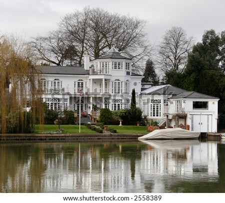 Winter scene of a Luxurious Residence and Boathouse on the banks of a River in England