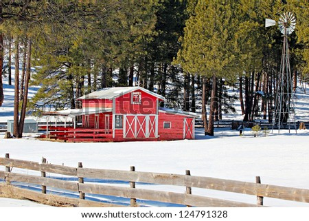 Winter scene of red barn trees snow and windmill - stock photo