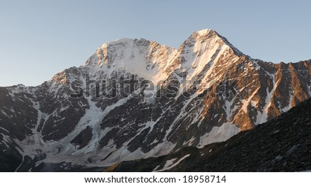 Winter scene of the tall mountain covered by snow