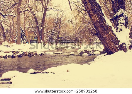 winter scene on a boulder stream through town with a retro instagram filter - stock photo
