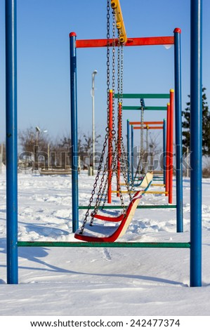 Winter scene with couple of swings in park - stock photo