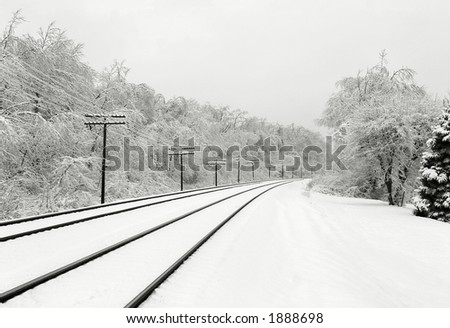 Winter scene with train tracks and snow-covered trees. - stock photo