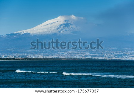 winter sea and Etna Vulcan eruption in the back.