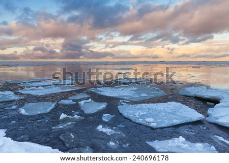 Winter Sea coastal landscape with big floating ice fragments on still cold water. Gulf of Finland, Russia - stock photo
