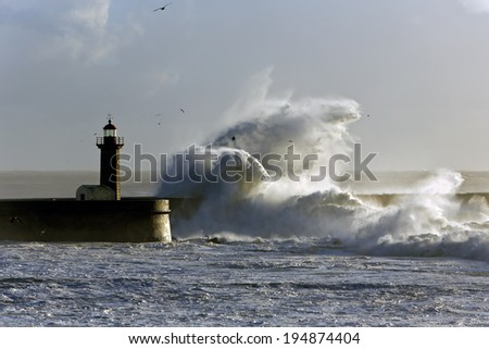 Winter seascape at sunset. Big wave against Porto old lighthouse.  - stock photo