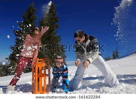 Winter season. Happy family having fun on fresh snow on vacation. - stock photo