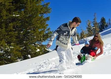 Winter season. Happy family having fun on fresh snow on vacation.