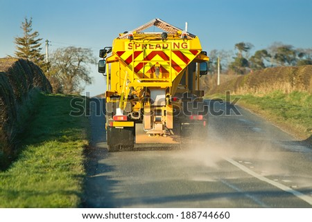 winter service vehicle or gritter spreading rock salt on the road surface to prevent icing in winter which causes accidents when vehicles slip on the highway. - stock photo