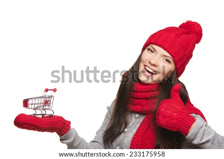 Winter shopping concept. Closeup of happy beautiful woman in winter red hat and scarf holding small empty shopping basket and gesturing thumb up, over white background - stock photo