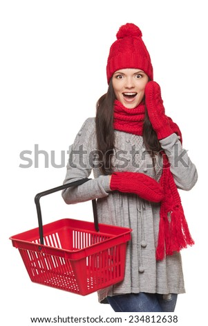 Winter shopping concept. Excited surprised girl in winter hat and scarf holding empty shopping basket, on white background - stock photo