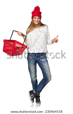 Winter shopping concept. Full length of happy girl in winter hat and scarf  holding empty shopping basket and gesturing thumb up, on white background - stock photo