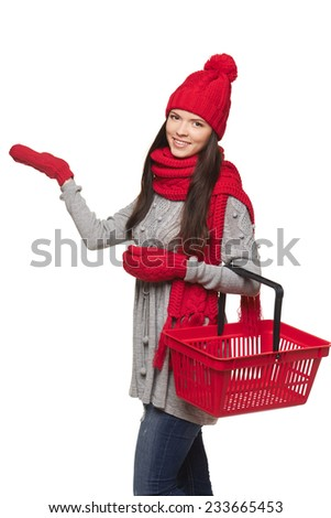 Winter shopping concept. Happy girl in winter hat and scarf holding empty shopping basket and showing blank copy space, on white background