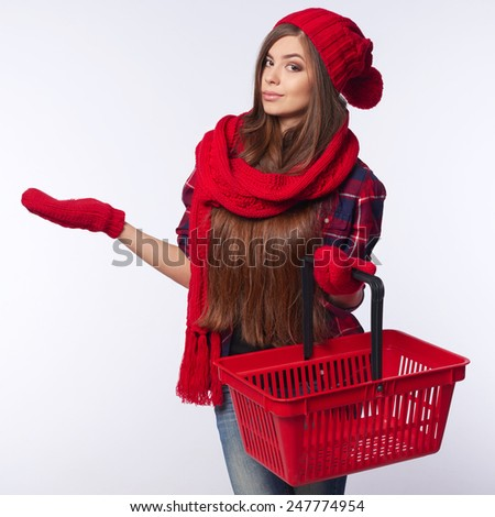 Winter shopping concept. Smiling beautiful woman in winter red hat and muffler holding empty shopping basket and showing open palm blank copy space over gray background - stock photo