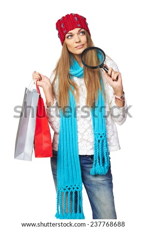 Winter shopping search concept. Thinking beautiful woman in winter hat and scarf holding shopping bags and holding magnifying glass, looking up at blank copy space making choice, over white background - stock photo