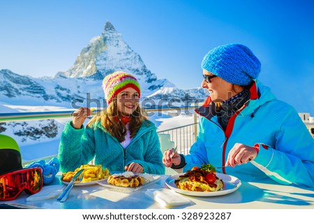 Winter, ski - skiers enjoying break for lunch, mountain view Matterhorn