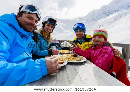 Winter, ski - skiers enjoying lunch in winter mountains - stock photo