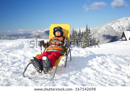 Winter, ski, sun and fun - happy girl skier in winter resort resting in the deck chair - stock photo