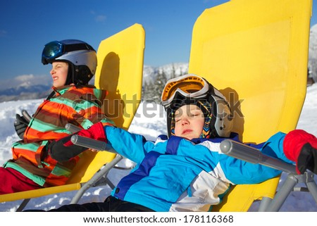 Winter, ski, sun and fun - portrait of kids in winter resort resting in the deck chair