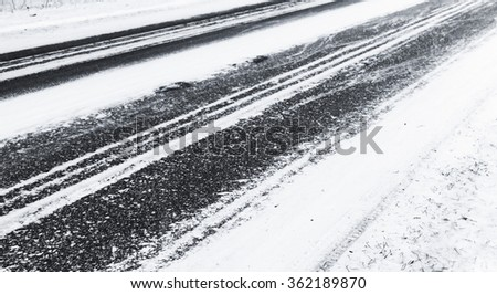 Winter slippery road background, black asphalt pavement under fresh snow layer - stock photo