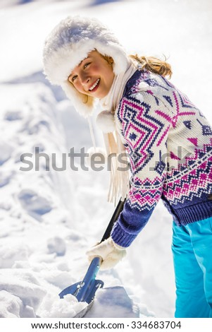 Winter, Snow removal - young girl with the snow shovel - stock photo