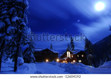 Winter snow scene of a cabin at Lake Kachess at night with moonlight. - stock photo