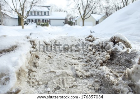 Winter snow tire marks in a driveway - stock photo