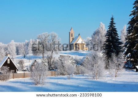 Winter snowy landscape with a church lit by the sun, Czech Republic