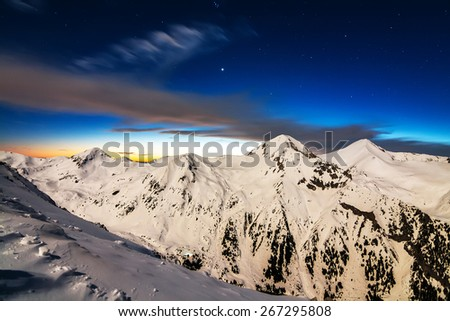 Winter Snowy Mountain Ridge in the Night Illuminated by the Moon at Long Exposure - stock photo