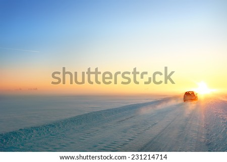 Winter snowy road and car at sunset - stock photo