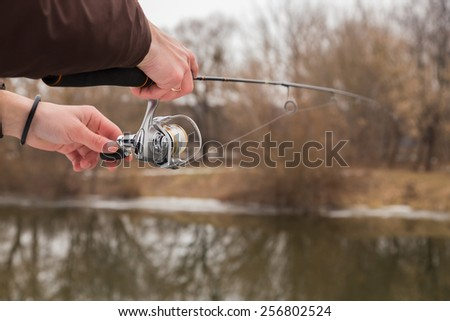 Winter spinning. Fishing in winter. Fisherman on the river bank. Fisherman holding a light spinning rod in his hand. Suburban recreation, sport fishing. Active Life on a fishing trip.  - stock photo