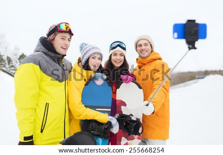 winter sport, leisure, friendship, technology and people concept - happy friends with snowboards and smartphone taking selfie - stock photo