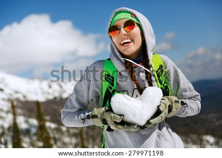 Winter sport, snowboarding - portrait of young snowboarder girl With snow heart in hands - stock photo