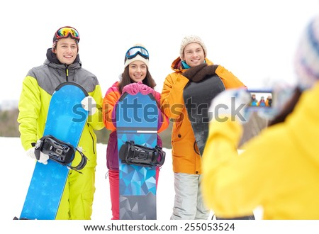 winter sport, technology, leisure, friendship and people concept - happy friends with snowboards and smartphone taking picture outdoors - stock photo