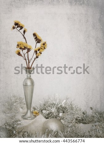 Winter still life. With silver baubles, tinsel etc. Elegant retro textured background. Christmas or general festive, seasonal. Yellow helichrysum flowers. - stock photo