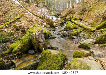 Winter stream / Stream running downhill over moss covered stones in winter