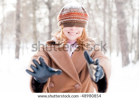 winter street portrait of young beautiful natural looking woman smiling and playing hide and seek with hat closing her eyes