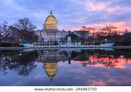 Winter sunrise at the illuminated US Capitol in Washington DC mirrored in the reflecting pool with dome under scaffolding for restoration. - stock photo