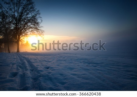 Winter sunrise over Lake Elk shore covered with snow. Masuria, Poland. - stock photo