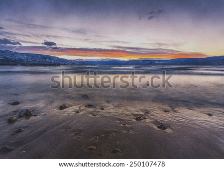 Winter Sunset at Lake Shore with a Vintage Color Filter Effect - stock photo