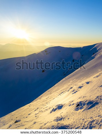 Winter sunset in the mountains. Direct sunlight. Sun beam. Light reflected from the snow. Steep slope. Clear blue sky. Deep shadows. Ukraine - stock photo