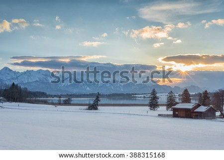 winter sunset landscape with lake mountains and trees