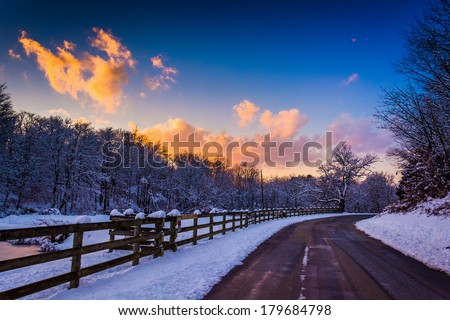 Winter sunset over a fence and country road in rural York County, Pennsylvania. - stock photo
