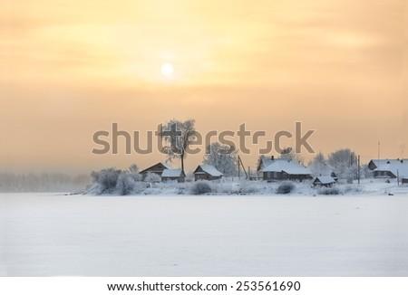 Winter sunset over village on frozen lake shore - stock photo