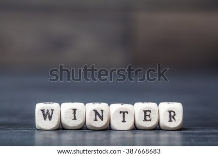 Winter text on wooden white cubes on wooden background with free space for text