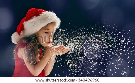 winter time! Happy little girl blowing on snow - stock photo