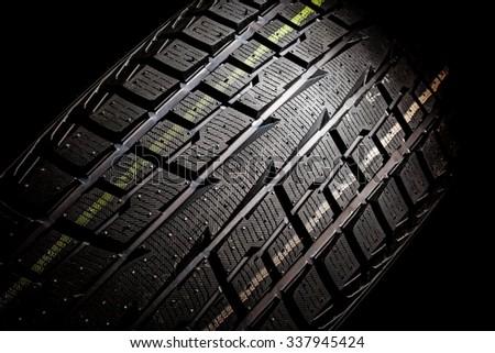 Winter tire on a black background, studio shot - stock photo